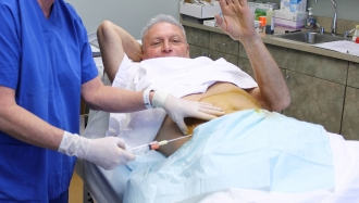 Our patient waves as fat is removed for a stem cell treatment to his knee