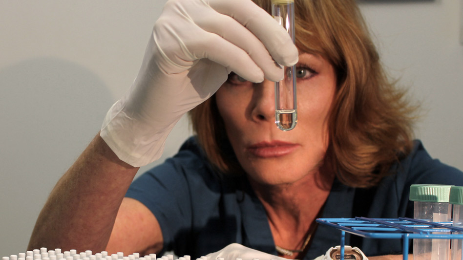 Woman looking at test tube of fluid suggesting stem cells