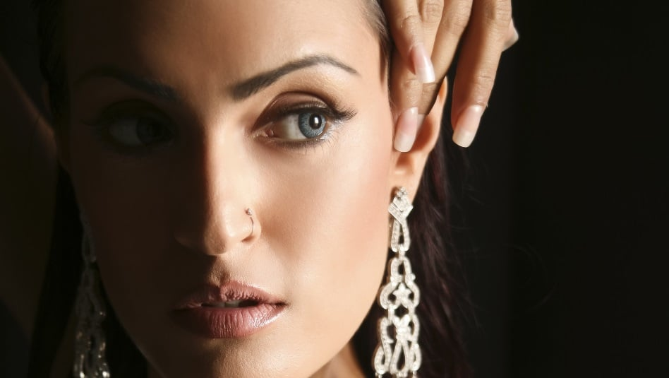 exotic looking woman's half face with dangling earring