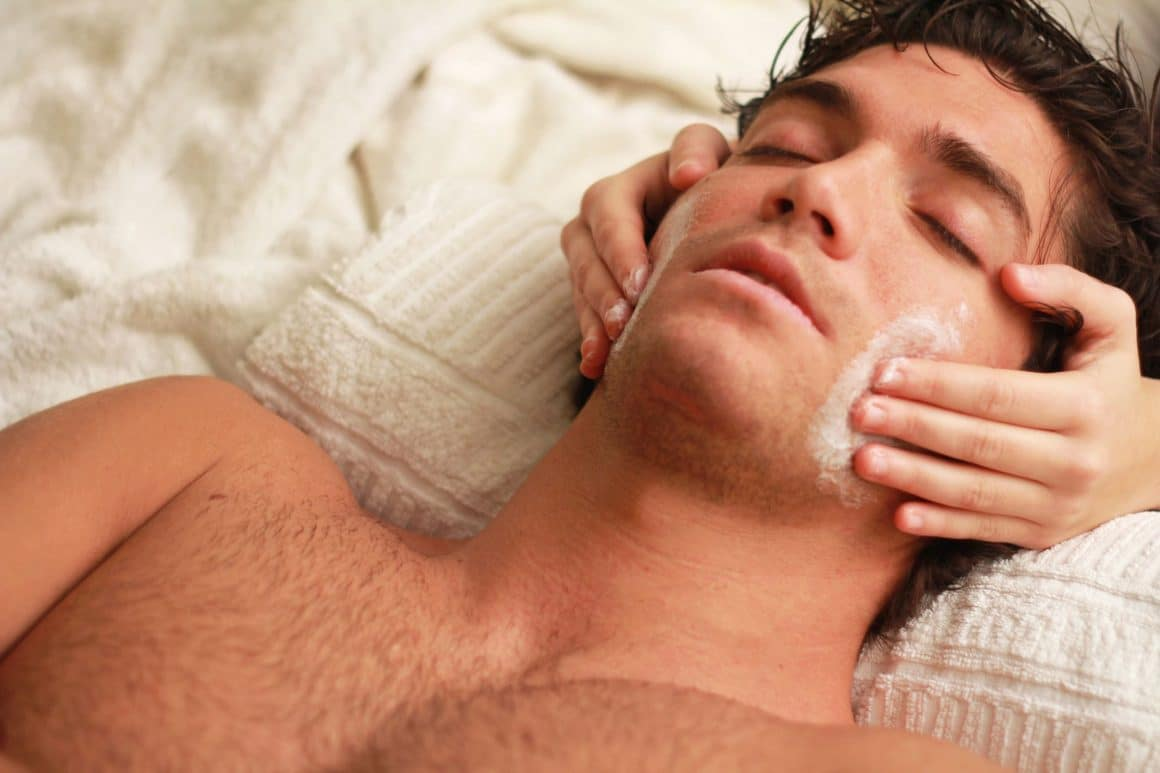 shirtless man lying on pillow with eyes closed having face cleansed