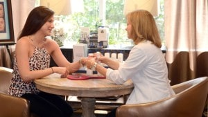 2 women sitting across each other at table with one's hand in the others