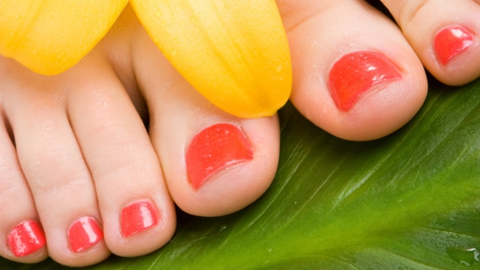close up of red toes & yellow flower