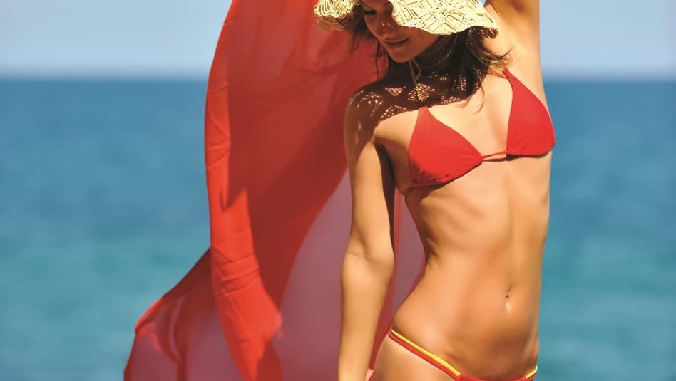 woman in red bikini holding up red towel behind her