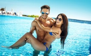 Couple with perfect bodies in sunglasses at beach