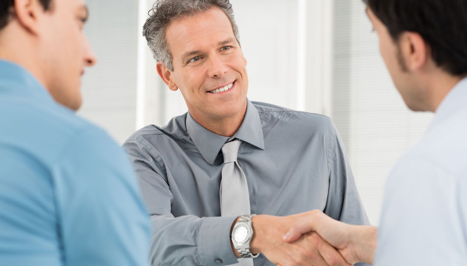 Confident mature man shaking hands with younger man